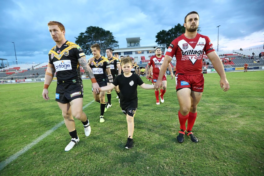 Olliver Ackerman walks onto the field, holding the hands of both captains. Photo: QRL Media