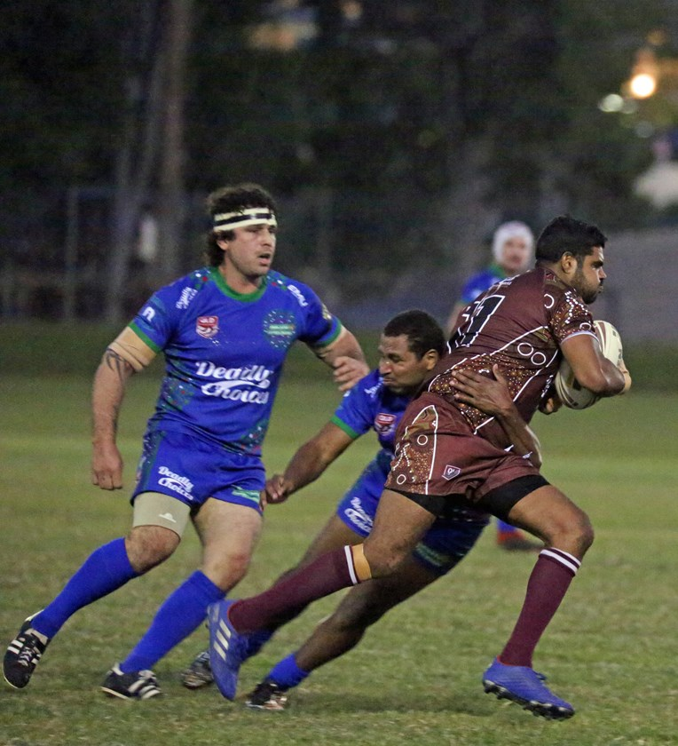 Yarrabah's Ashton Schrieber tries to break out of the clutches of Innisfail player Elia Mooka. Photo: Maria Girgenti
