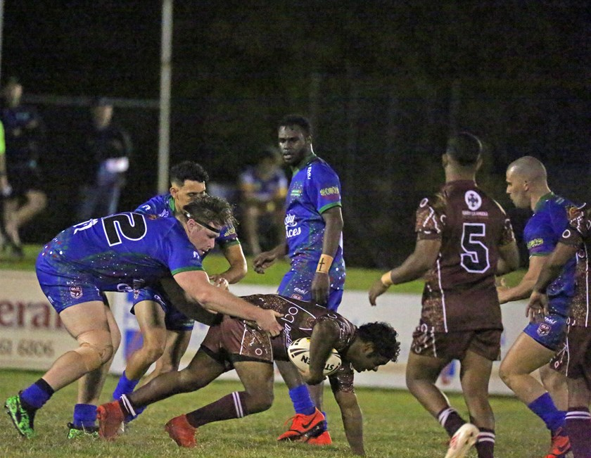 A Yarrabah player is pulled back by Innisfail's Jaymon Moore. Photo: Maria Girgenti