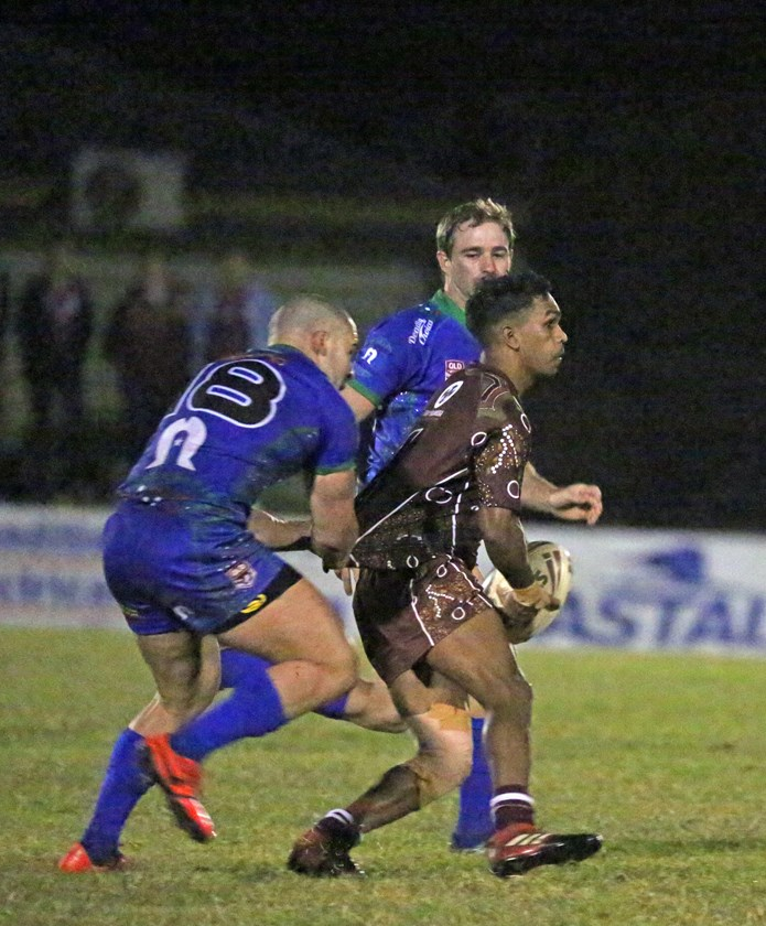 Yarrabah's Andrew Garrett Jnr looks for support after being halted by Innisfail player Chris Galea. Photo: Maria Girgenti