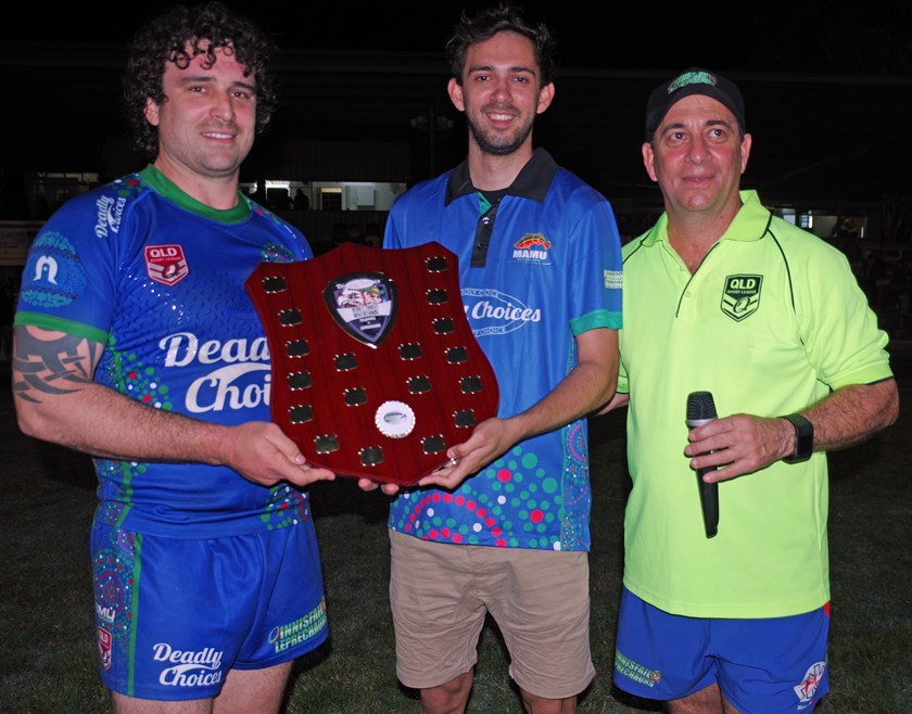 Denzel Philpot from Mamu Health Service Deadly Choices program and Innisfail Brothers president Nick Souvlis presented the Deadly Choices Invitational shield to winning Innisfail captain Robert Haren. Photo: Maria Girgenti