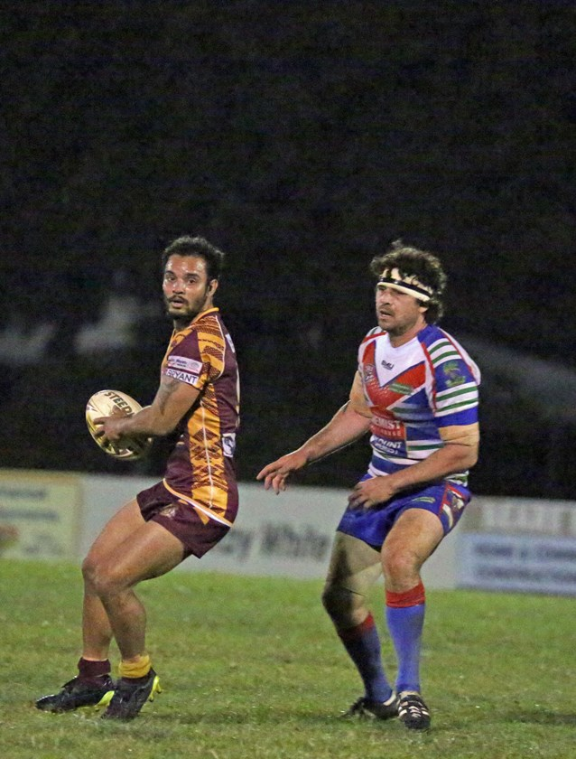 Suburbs player Roland Gallen breaks away from Innisfail's Robert Haren and plans his next move. Photo: Maria Girgenti