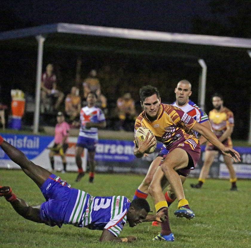 Suburbs player Richard Joinbee evades the grip of Innisfail's Den Waireg-Ingui. Photo: Maria Girgenti