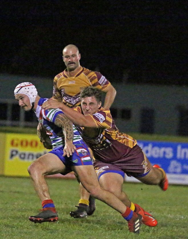 Southern Suburbs player Taj Walker latches onto Innisfail's Aaron Jolley. Photo: Maria Girgenti