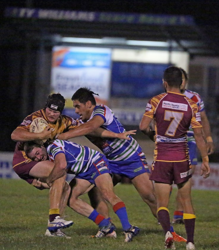 Southern Suburbs try scorer Ryley Archibald is wrapped up by Innisfail players Luke Horsford and Joel Lokotui. Photo: Maria Girgenti