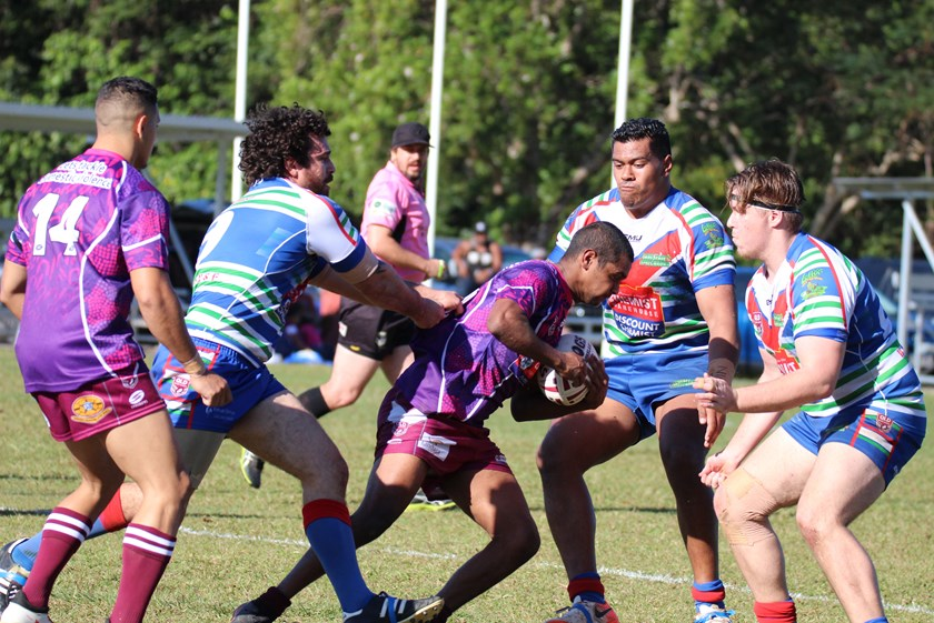 A Yarrabah player is surrounded by Innisfail's Robert Haren, Taulata Fakalelu and Jaymon Moore Photo: Maria Girgenti