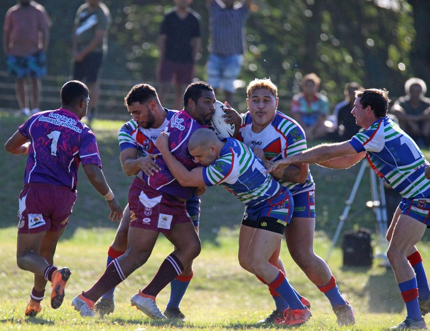 A Yarrabah player is stopped in his tracks by Innisfail players Ronald Ambrum, Chris Galea, Usaia Fonongaloa and Luke Horsford Photo: Maria Girgenti