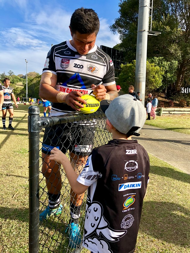 Tevita Folau signs a ball for a young fan. Photos: Tweed Heads Seagulls Media